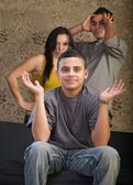 Grinning Young Man with Angry Parents — Stock Photo