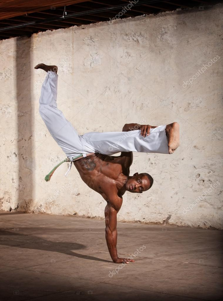Strong African man demonstrating a Capoeria one armed kick  Stock Photo #13127761