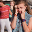 Stock Photo: Teenagers Laughing at Scared Girl
