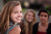 Usmívající se dospívající dívka s dvěma přáteli — Stock fotografie