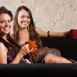 Two Grinning Ladies Sitting on Sofa — Stock Photo