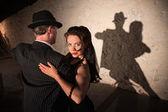 Twee tango dansers het uitvoeren van in schijnwerpers binnenshuis — Stockfoto