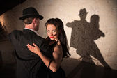 Two tango dancers performing under spotlight indoors — Stok fotoğraf