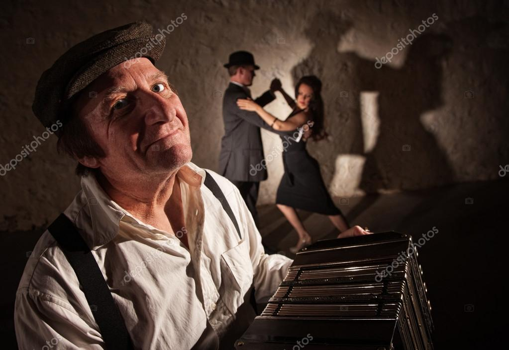 Smiling accordion player performing with dancers in the background — Stock Photo #13607337