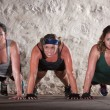 Foto Stock: Three Women Do Push Ups in Boot Camp Workout