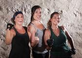 Três senhoras de treino estilo boot camp flex seus bíceps — Foto Stock