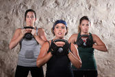 Dames opheffing kettlebells in kamp van de laars stijl training — Stockfoto