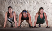 Three Women Do Push Ups in Boot Camp Workout — Стоковое фото