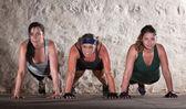 Três mulheres push ups no boot camp workout — Foto Stock