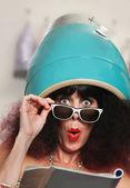 Mulher lendo sob o secador de cabelo — Foto Stock