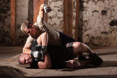 Martial Artist Punching Man on Ground — Stock Photo