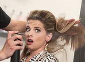 Stylista używa lakieru na zaskoczony kobieta — Zdjęcie stockowe