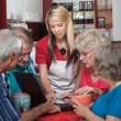 Helpful Waitress with Seniors on Laptop — Stock Photo