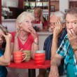 Embarrassed Seniors with Loud Friend — Stock Photo
