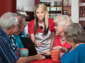 Seniors with Laptop and Helpful Waitress — Stock Photo