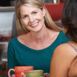 Smiling Blond Woman with Friend in Bistro — Stock Photo