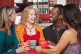 Radostné skupina čtyř v kavárně — Stock fotografie