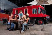 едят пиццу возле фургона с продуктами — Стоковое фото