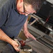 Stock Photo: Artist Rolling Hot Glass Piece