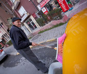 Unidentified cabbie washing taxi on street in Turkey — 图库照片