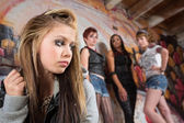 Mean Group Near Sad Girl — Stock Photo