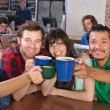 Stock Photo: Joyful Group Holding Mugs