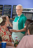 Smiling Cafe Worker with Customers — Stock Photo