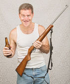 Man with Rifle and Beer — Stock Photo