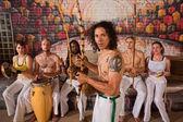 Intérprete de capoeira latino com grupo — Fotografia Stock