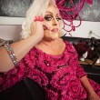 Foto Stock: Blond Drag Queen Sitting
