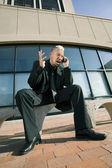 Gefrustreerd punk zakenman op zijn mobiele telefoon — Stockfoto