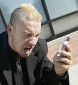 Frustrated Punk Businessman on his Cell Phone — Stock Photo