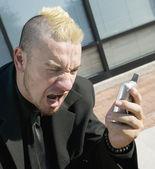разочарованный панк-бизнесмен на свой мобильный телефон — Стоковое фото