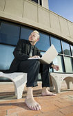 Barefoot Punk Businessman with his Laptop Computer — Stock Photo