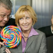 Stock Photo: Min office offers coworker lollipop
