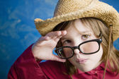Little girl with glasses and a straw hat — Stock Photo
