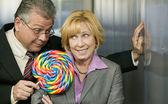 Man in office offers coworker a lollipop — Stock Photo