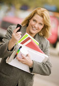 Woman with many books on a sidewalk — Stock Photo