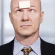 Businessman with a blank note on his forehead — Stock Photo #39601851
