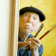 Artist with a Beret at a Canvas looking at model — Stock Photo #39602405