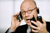 Businessman with multiple cell phones — Stockfoto