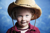 Little girl in front of blue wall with a cowboy hat — Stock Photo