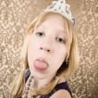 Stock Photo: Pretty young girl with tiarsticking her tongue out