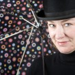 Woman in a bowler hat with umbrella — Stock Photo