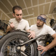 Stock Photo: Two Motorcycle Mechanics Placing Fender