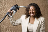 Woman Holding Gas Nozzle to her Head — Stockfoto