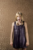 Young blonde girl with braces screams — Stock Photo