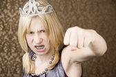Pretty young girl with a tiara throws a punch — Stock Photo