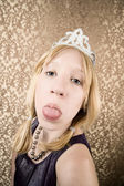 Pretty young girl with a tiara sticking her tongue out — Stock Photo