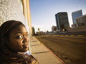 African American Woman Leaning against a Building — Stock Photo